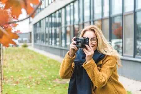 Photo pour Élégant belle femme prenant des photos de l'arbre d'automne - image libre de droit
