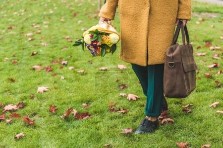 woman with bouquet and bag