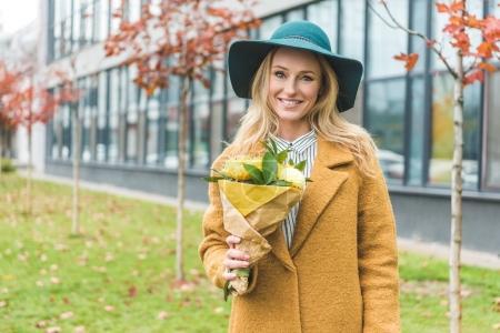 Photo pour Jolie femme élégante en manteau jaune et chapeau de feutre tenant le bouquet - image libre de droit