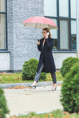 woman with umbrella and smartphone