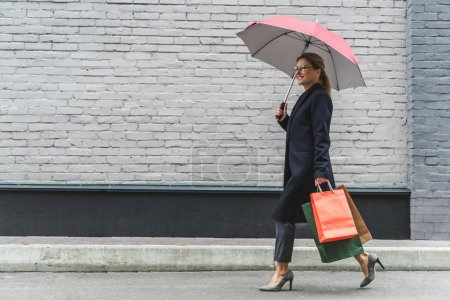 woman with umbrella and shopping bags