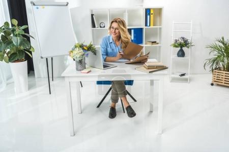 Photo pour Élégante femme d'affaires qui travaillent avec des documents et ordinateur portable au lieu de travail dans les bureaux modernes - image libre de droit