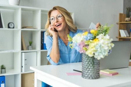 Photo pour Belle femme d'affaires gai parler sur smartphone au lieu de travail dans le bureau moderne - image libre de droit