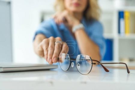 Photo pour Vue recadrée de la femme d'affaires tenant des lunettes sur le lieu de travail - image libre de droit