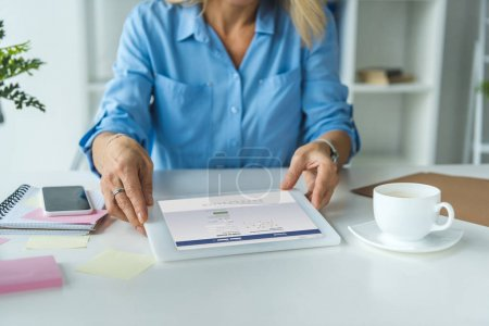 Photo for Cropped view of businesswoman using digital tablet with facebook website - Royalty Free Image