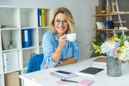 Photo pour Attrayant mature femme d'affaires ayant pause café sur le lieu de travail avec des appareils numériques - image libre de droit
