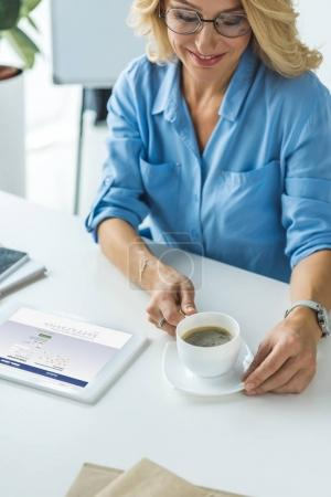 Businesswoman using tablet with facebook website