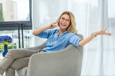 Photo pour Attrayante femme souriante à l'aide de smartphone tout en étant assis sur le fauteuil de bureau - image libre de droit