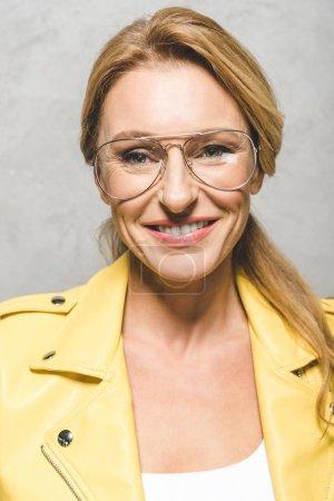 Photo pour Portrait de belle femme blonde mature en lunettes et veste en cuir jaune - image libre de droit