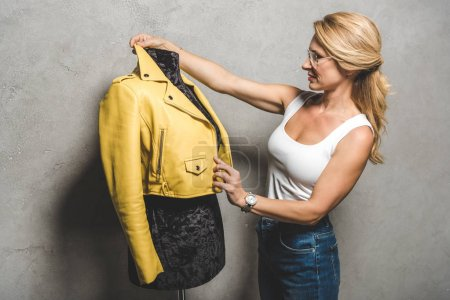 Photo for Attractive mature dressmaker with yellow leather jacket on mannequin - Royalty Free Image