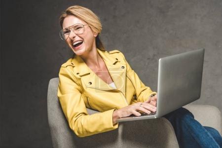 laughing woman using laptop