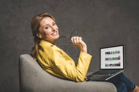 Photo for Smiling mature woman using laptop with youtube website and sitting in armchair - Royalty Free Image
