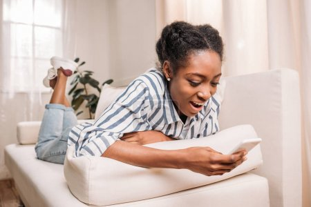 woman on couch using smartphone