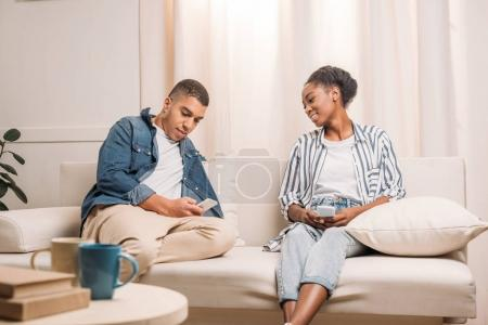 couple sitting with smartphones