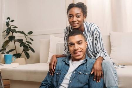 Photo for Happy african american smiling couple sitting together on sofa at home and looking at camera - Royalty Free Image