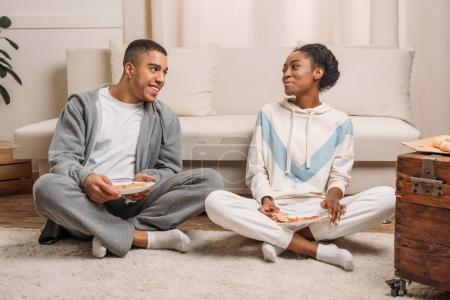 couple eating pizza beside sofa