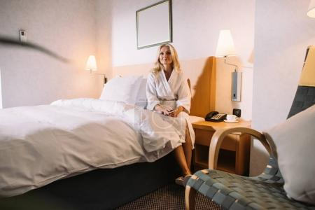 mature woman with smartphone in hands sitting on bed and looking away in hotel room