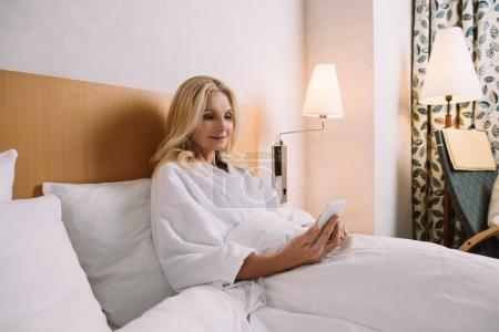 beautiful smiling woman in bathrobe using smartphone while lying in bed at hotel room