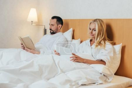 mature couple with digital tablet and book lying together in bed at hotel room