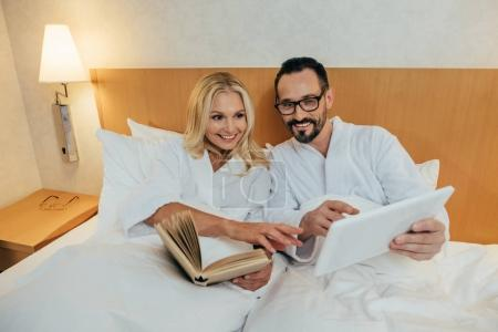 smiling mature couple reading book and using digital tablet while lying together in bed in hotel room