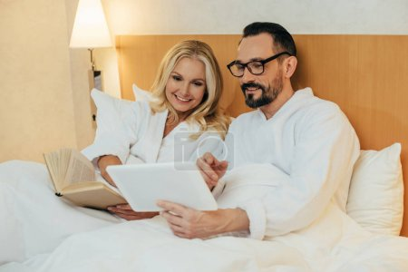 happy middle aged couple reading book and using digital tablet while lying together in bed in hotel room