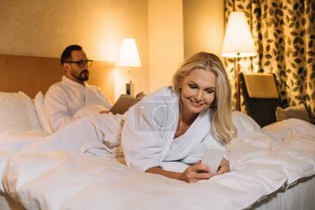 Photo pour Femme en peignoir, allongé sur le lit et à l'aide de smartphone tout en livre de lecture mari derrière souriant moyen d'âge - image libre de droit