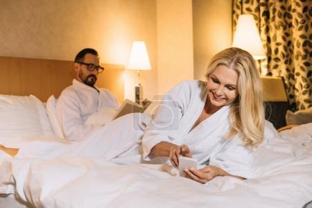 Photo pour Belle femme souriante d'âgé moyenne en peignoir, allongé sur le lit et à l'aide de smartphone tout en livre de lecture mari derrière - image libre de droit
