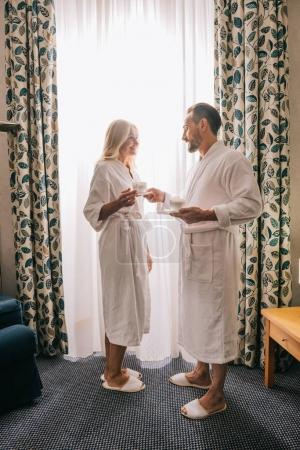 full length view of happy mature couple in bathrobes drinking coffee and smiling each other in hotel room