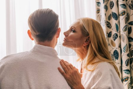profile view of mature woman able to kiss her husband wearing bathrobe in hotel room