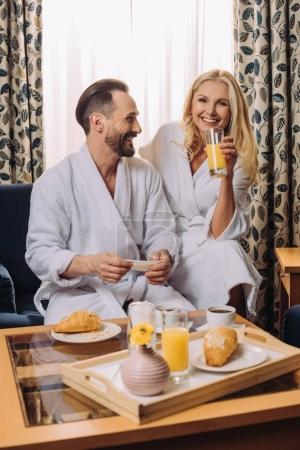 happy middle aged couple in bathrobes having breakfast together in hotel room