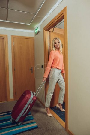 Photo for Beautiful happy middle aged woman with suitcase entering hotel room - Royalty Free Image
