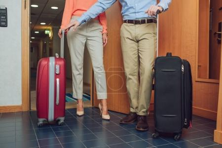 cropped shot of mature couple with suitcases entering into hotel room