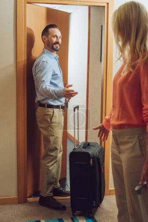 mature couple with suitcases entering into hotel room