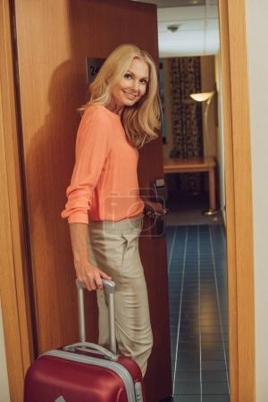 beautiful smiling mature woman with suitcase looking at camera while entering hotel room