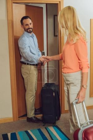mature couple with suitcases holding hands while entering into hotel room