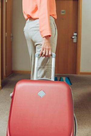 cropped shot of woman with suitcase walking through hotel hallway