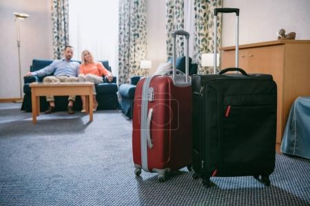 close-up view of two suitcases and mature couple sitting on sofa in hotel room