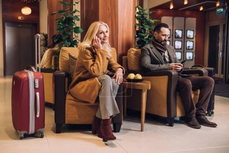 Photo for Middle aged couple using smartphones while waiting with suitcases in hotel - Royalty Free Image