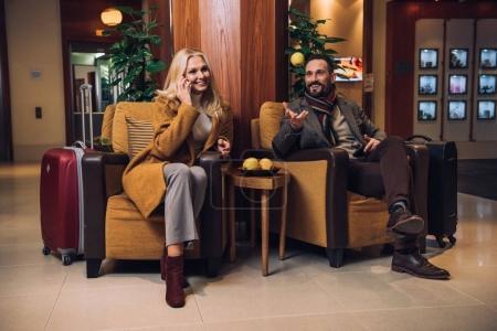 Photo pour Heureux couple senior parlant et en utilisant le smartphone tout en étant assis sur le couloir de l'hôtel - image libre de droit