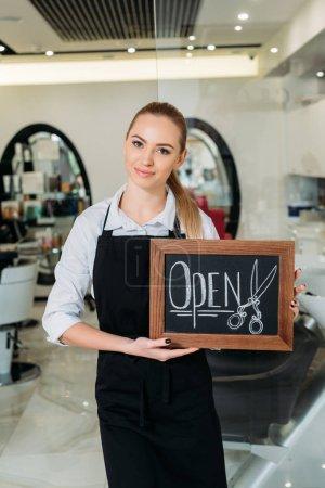 smiling blonde hairdresser showing sign open