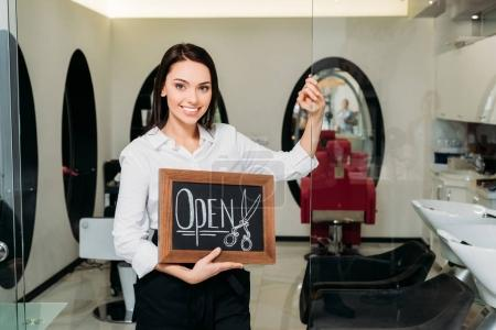 smiling owner of hair salon standing with sign open and leaning on glass door