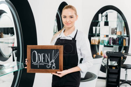 attractive hairdresser holding sign open