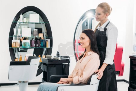 happy hairdresser and customer looking at new hairstyle