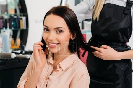 Photo pour Image recadrée de femme parlant par smartphone au salon de coiffure - image libre de droit