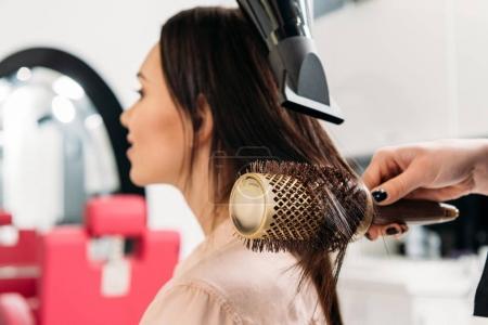 Photo pour Image recadrée de coiffeur coiffant cheveux avec brosse à cheveux ronde - image libre de droit