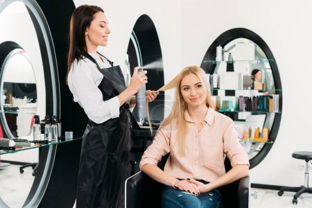 Photo pour Salon de coiffure souriant appliquant de la laque - image libre de droit