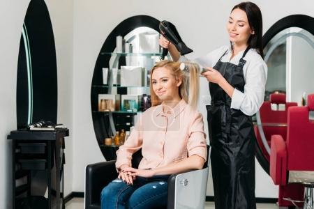 smiling hairdresser drying customer hair at salon