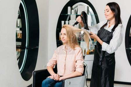 hairdresser drying customer hair at salon
