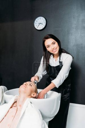 happy hairdresser washing customer hair and looking at camera