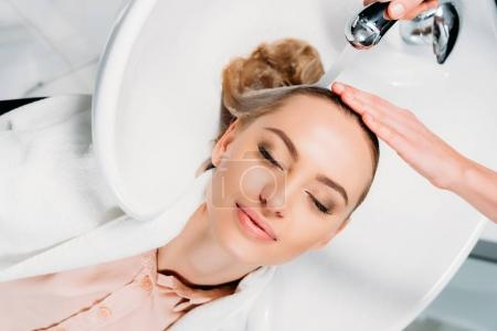 top view of customer with closed eyes lying above washbasin while hairdresser washing hair
